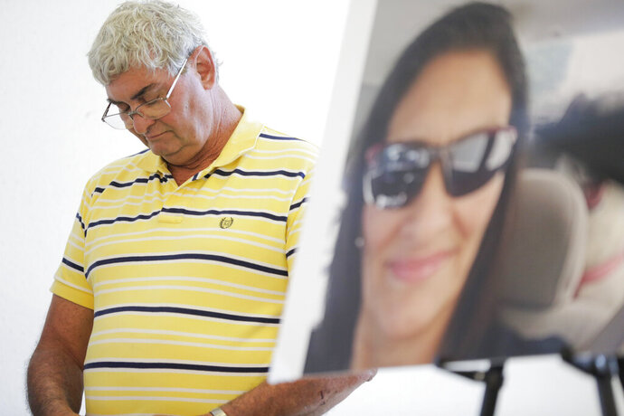 FILE - In this  July 25, 2019 file photo John Nicholas, brother of Rhogena Nicholas, lowers his head next to a photo of his sister during a news conference in Houston.  A former Houston police officer has been charged with felony murder in connection with a deadly January drug raid that killed a couple and injured several officers, prosecutors announced Friday, Aug. 23.  Killed in the shooting were 58-year-old Rhogena Nicholas and 59-year-old Dennis Tuttle.(Elizabeth Conley/Houston Chronicle via AP)
