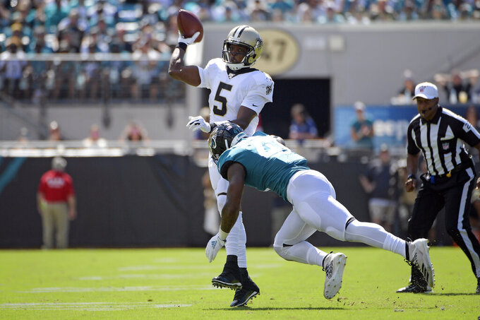 New Orleans Saints quarterback Teddy Bridgewater (5) throws a pass as he is hit by Jacksonville Jaguars defensive end Josh Allen during the first half of an NFL football game, Sunday, Oct. 13, 2019, in Jacksonville, Fla. (AP Photo/Phelan M. Ebenhack)