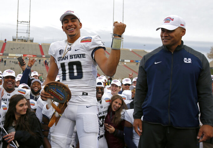 FILE - In this Dec. 15, 2018, file photo, Utah State quarterback Jordan Love (10) celebrates after being named the Outstanding Offensive Player as interim head coach Frank Maile looks on, following the New Mexico Bowl NCAA college football game against North Texas, in Albuquerque, N.M. Before he blossomed into a Heisman Trophy candidate, Utah State quarterback Jordan Love threw his first career touchdown pass at Wake Forest.  He's looking to fling a few more in his return trip _ and to finish with a different result. (AP Photo/Andres Leighton, File)