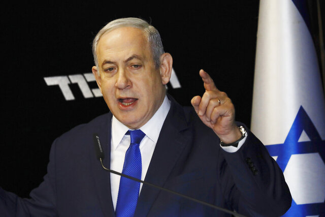 Israeli Prime Minister Benjamin Netanyahu deliverers a statement at the airport city in Lod Israel, Friday, Dec. 27, 2019. Netanyahu shored up his base with a landslide primary victory announced early Friday, but he will need a big win in national elections in March if he hopes to stay in office and gain immunity from prosecution on corruption charges. (AP Photo/Ariel Schalit)