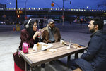 """In this Dec. 27, 2019, photo, Amani Al-Khatahtbeh, founder of MuslimGirl.com, left, sips a soda while talking with old friends Mohammed Ali, right, and Saad Khan outside of a corner market in the Brooklyn borough of New York. Al-Khatahtbeh stays in New Jersey with her family when in town on business. Her home and office are in Los Angeles. Growing up, she remembers not having many friends and was often bullied. """"High school kind of like made me into the person that I needed to be to create MuslimGirl,"""" she says. (AP Photo/Jessie Wardarski)"""