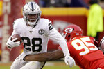 Oakland Raiders running back Josh Jacobs (28) tries to break a tackle by Kansas City Chiefs defensive tackle Chris Jones (95) during the first half of an NFL football game in Kansas City, Mo., Sunday, Dec. 1, 2019. (AP Photo/Charlie Riedel)