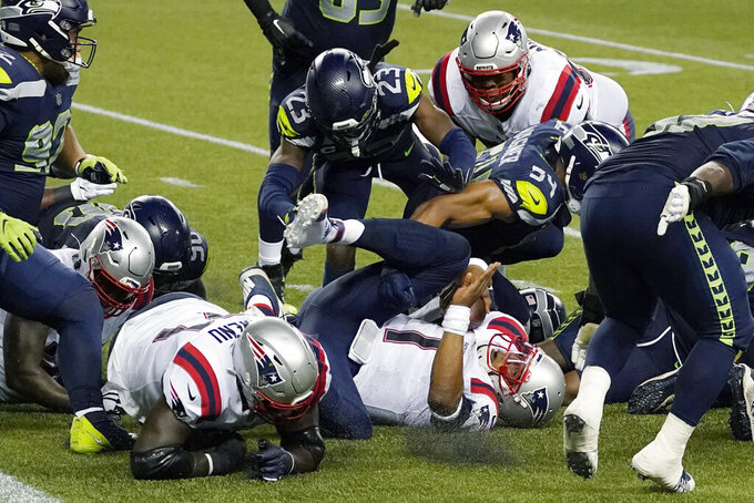 New England Patriots quarterback Cam Newton comes down on his back after he was stopped near the goal line as the clock expires in the fourth quarter of an NFL football game against the Seattle Seahawks, Sunday, Sept. 20, 2020, in Seattle. The Seahawks won 35-30. (AP Photo/Elaine Thompson)