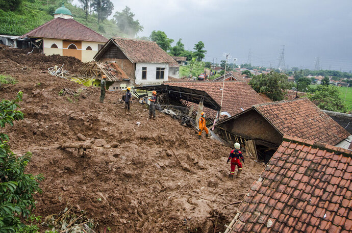 Rescuers search for victims at a village hit by Sunday's landslides in Sumedang, West Java, Indonesia, Monday, Jan. 11, 2021. Landslides triggered by heavy rain in the village left at a number of people died and injured, officials said. (AP Photo/Sorasoca)