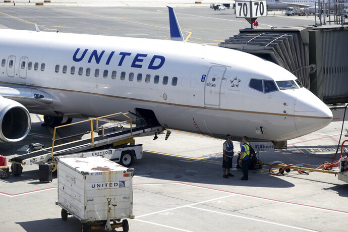 FILE - In this July 18, 2018, file photo a United Airlines commercial jet sits at a gate at Terminal C of Newark Liberty International Airport in Newark, N.J.  United Airlines plans to furlough about 16,000 employees in October 2020 as air travel continues to be hammered by the pandemic. That's fewer furloughs than United predicted in July, when it warned 36,000 employees that they could lose their jobs.  (AP Photo/Julio Cortez, File)