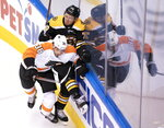 Philadelphia Flyers center Derek Grant (38) and Boston Bruins defenseman Jeremy Lauzon (79) mix it up along the boards during first-period NHL hockey playoff action in Toronto, Sunday, Aug. 2, 2020. (Frank Gunn/The Canadian Press via AP)