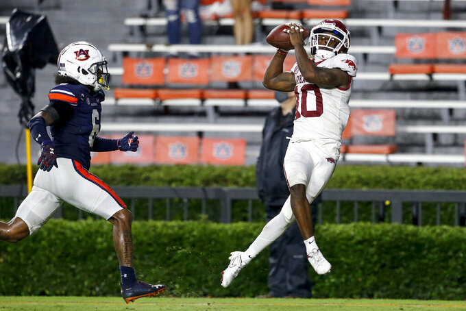 Arkansas wide receiver De'Vion Warren (10) catches a pass for a touchdown as Auburn defensive back Christian Tutt (6) defends during the second half of an NCAA college football game on Saturday, Oct. 10, 2020, in Auburn, Ala. (AP Photo/Butch Dill)