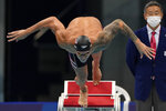 Caeleb Dressel, of the United States, starts the men's 100-meter butterfly final at the 2020 Summer Olympics, Saturday, July 31, 2021, in Tokyo, Japan. (AP Photo/Gregory Bull)