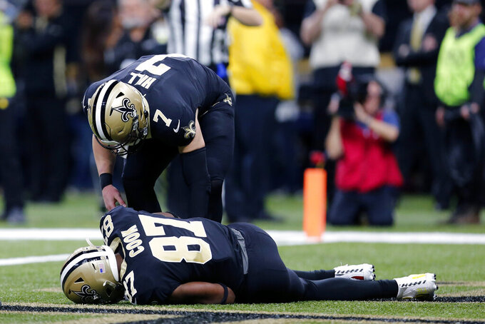 New Orleans Saints quarterback Taysom Hill (7) tends to tight end Jared Cook (87) after Cook was hurt scoring on a touchdown reception in the first half an NFL football game against the San Francisco 49ers in New Orleans, Sunday, Dec. 8, 2019. (AP Photo/Brett Duke)