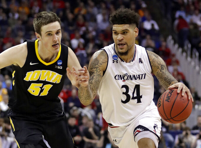 FILE - This March 22, 2019, file photo shows Cincinnati's Jarron Cumberland (34) driving past Iowa's Nicholas Baer (51) in the first half during a first round men's college basketball game in the NCAA Tournament in Columbus, Ohio. Mick Cronin left for UCLA, and Cincinnati turned to a familiar local coach, John Brannen, as his replacement. The Bearcats are undergoing significant changes in his first season. (AP Photo/Tony Dejak, File)