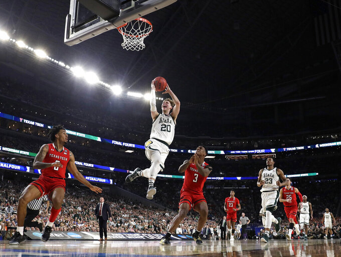 Michigan State guard Matt McQuaid (20) drives to the basket over Texas Tech's Kyler Edwards, left, and Deshawn Corprew (3) during the first half in the semifinals of the Final Four NCAA college basketball tournament, Saturday, April 6, 2019, in Minneapolis. (AP Photo/David J. Phillip)