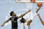 North Carolina forward Armando Bacot (5) drives to the basket while Wake Forest forward Isaiah Mucius (1) defends during the second half of an NCAA college basketball game in Chapel Hill, N.C., Wednesday, Jan. 20, 2021. (AP Photo/Gerry Broome)