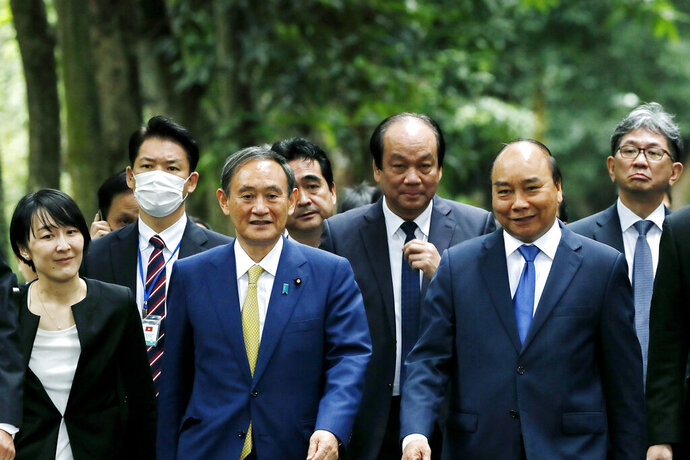Japanese Prime Minister Yoshihide Suga, center left, and his Vietnamese counterpart Nguyen Xuan Phuc, center right, visit the late President Ho Chi Minh's Stilt House in Hanoi, Vietnam, Monday, Oct. 19, 2020. Suga is on an official visit to Vietnam. (AP Photo/Minh Hoang, Pool)