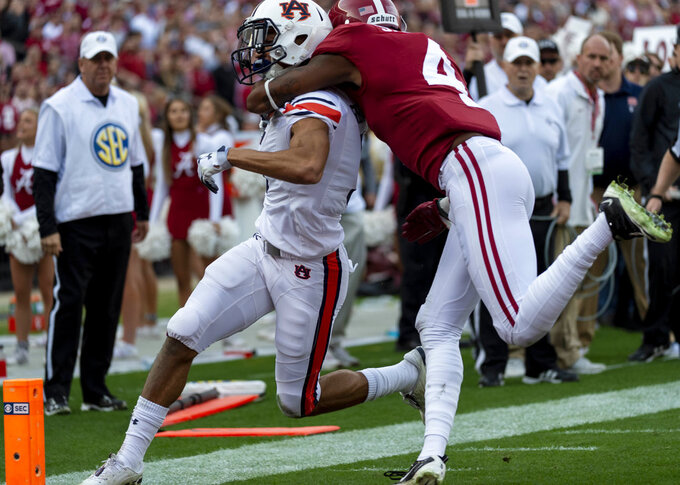 Auburn wide receiver Anthony Schwartz (5) scores his team's first touchdown as he is hit by Alabama defensive back Saivion Smith (4) during the first half of an NCAA college football game, Saturday, Nov. 24, 2018, in Tuscaloosa, Ala. (AP Photo/Vasha Hunt)