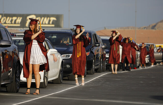 Graduates flip their tassels near their cars during a drive-thru graduation for Faith Lutheran High School at the Las Vegas Motor Speedway, Friday, May 22, 2020, in Las Vegas. The school held a special drive-thru graduation amid the coronavirus pandemic. (AP Photo/John Locher)
