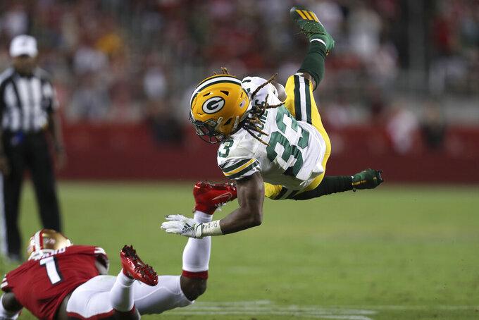 Green Bay Packers running back Aaron Jones (33) falls forward over San Francisco 49ers cornerback Jimmie Ward (1) during the second half of an NFL football game in Santa Clara, Calif., Sunday, Sept. 26, 2021. (AP Photo/Jed Jacobsohn)