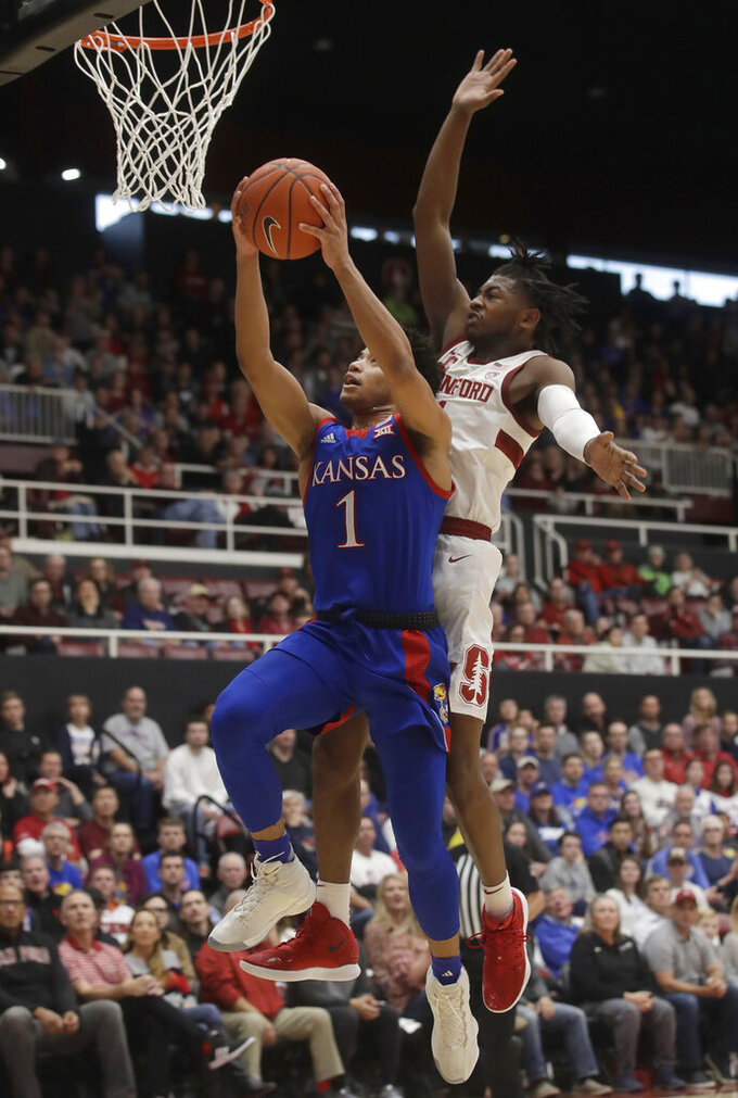 Kansas guard Devon Dotson, left, shoots against Stanford guard Daejon Davis during the first half of an NCAA college basketball game in Stanford, Calif., Sunday, Dec. 29, 2019. (AP Photo/Jeff Chiu)