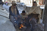 People sit around a fire to warm themselves after a heavy snowfall in Quetta, capital of Pakistan's southwestern Baluchistan province, Monday, Jan. 13, 2020. Severe winter weather has struck parts of Afghanistan and Pakistan, with heavy snowfall, rains and flash floods that left more than 40 dead, officials said Monday as authorities struggled to clear and reopen highways and evacuate people to safer places. (AP Photo/Arshad Butt)