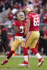 San Francisco 49ers quarterback Trey Lance, left, celebrates with offensive tackle Mike McGlinchey (69) after throwing a touchdown pass to wide receiver Trent Sherfield an NFL preseason football game against the Kansas City Chiefs in Santa Clara, Calif., Saturday, Aug. 14, 2021. (AP Photo/Tony Avelar)