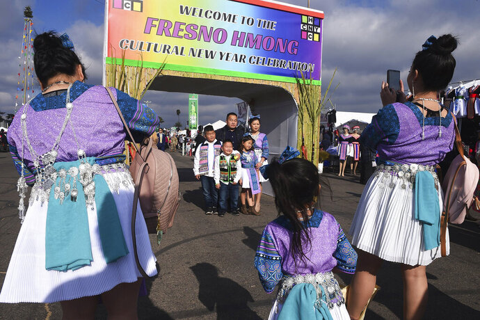 In this photo taken Jan. 27, 2018, a family poses at the entrance to the Hmong New Year Cultural Celebration in Fresno, Calif. The country's small Hmong American population is reeling from the shooting deaths of four men at a backyard party at a Northern California central valley city. Fresno hosts a week-long New Year's party every year that draws tens of thousands of Hmong from around the country, complete with colorful traditional dress, song, and sports games. (Eric Paul Zamora/The Fresno Bee via AP)/The Fresno Bee via AP)