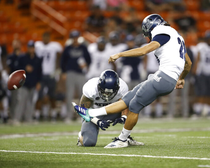 Nevada wide receiver Kaleb Fossum (3) holds the ball as Nevada place kicker Ramiz Ahmed (26) makes a field goal against Hawaii during the second quarter of an NCAA college football game Saturday, Oct. 20, 2018, in Honolulu. (AP Photo/Marco Garcia)
