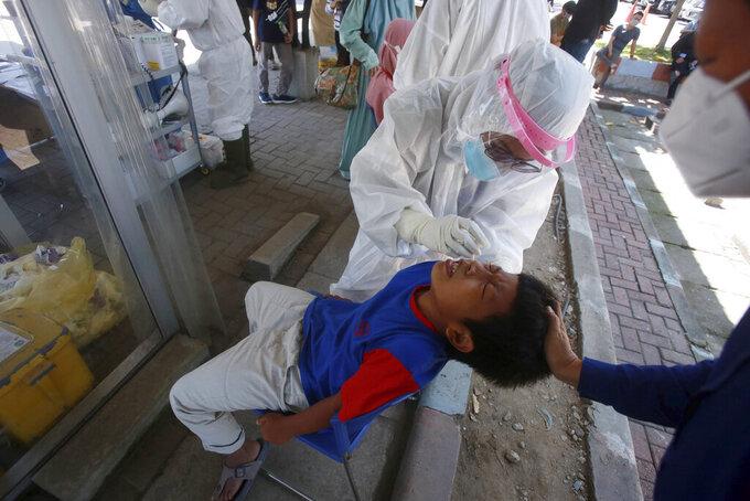 A ten years old boy gets a coronavirus test at the North Sumatra University hospital in Medan, North Sumatra, Indonesia, Thursday, July 22, 2021. (AP Photo/Binsar Bakkara)