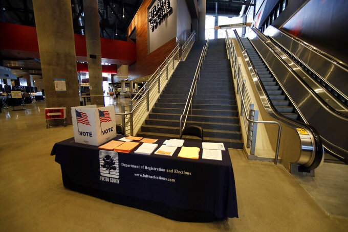 Voting equipment is shown during a media tour of State Farm Arena, home of the NBA's Atlanta Hawks basketball team, Friday, July 17, 2020, in Atlanta. The 16,888-seat facility will be used as a poll location for the upcoming election. (AP Photo/John Bazemore)