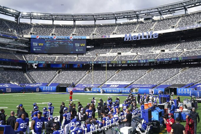 FILE - In this Sunday, Oct. 18, 2020, file photo, New York Giants players watch their teammates during the first half of an NFL football game against the Washington Football Team in East Rutherford, N.J.New Jersey Gov. Phil Murphy conditionally vetoed a bill on Monday, Oct. 19, 2020, that would have expanded charitable groups' ability to sell raffle tickets online based around sporting events, determining it was too close to internet gambling. Because the coronavirus pandemic has drastically reduced or even eliminated in-person attendance, some legislators proposed letting people buy tickets to such raffles over the internet, regardless of whether they were in a stadium or not. (AP Photo/John Minchillo, File)
