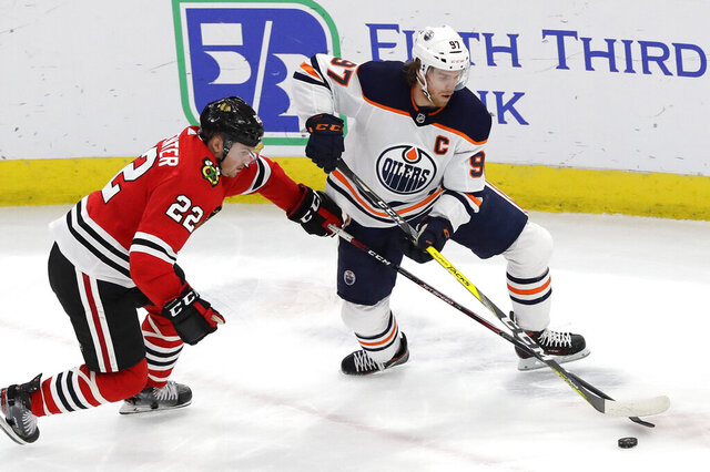FILE - In this March 5, 2020, file photo, Edmonton Oilers center Connor McDavid, right, and Chicago Blackhawks center Ryan Carpenter vie for the puck during the first period of an NHL hockey game in Chicago. The Oilers say McDavid has tested positive for COVID-19. The team says the star forward is self-quarantining at home and experiencing mild symptoms. (AP Photo/Nam Y. Huh, File)