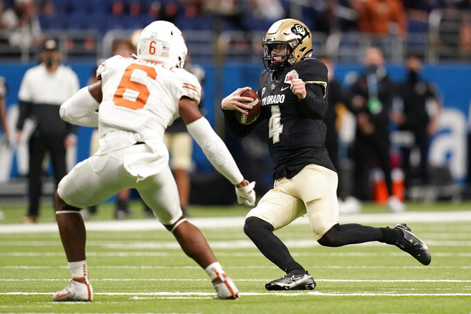Colorado quarterback Sam Noyer (4) prepares to slide as Texas linebacker Juwan Mitchell (6) defends during the second half of the Alamo Bowl NCAA college football game Tuesday, Dec. 29, 2020, in San Antonio. (AP Photo/Eric Gay)