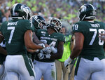 Michigan State's Elijah Collins, center, celebrates his rushing touchdown with teammates during the fourth quarter of an NCAA college football game against Arizona State, Saturday, Sept. 14, 2019, in East Lansing, Mich. (AP Photo/Al Goldis)