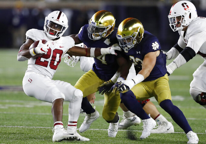 FILE - In this Sept. 29, 2018, file photo, Stanford running back Bryce Love (20) is stopped by Notre Dame linebackers Te'von Coney (4) and Drue Tranquill (23) during the second half of an NCAA college football game in South Bend, Ind. Love has struggled to get going this year for Stanford. He is averaging 4.3  yards per carry, down from a mark 8.1 a year ago, and already missed one game against UC Davis to heal up some bumps and bruises. He left last week's game against the Irish with an injured ankle and is questionable for this week's game against Utah. (AP Photo/Carlos Osorio, File)