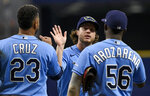 Tampa Bay Rays' Nelson Cruz (23), Brett Phillips and Randy Arozarena (56) celebrate a three-game sweep against the Miami Marlins after a 3-2 win in a baseball game Sunday, Sept. 26, 2021, in St. Petersburg, Fla. (AP Photo/Steve Nesius)