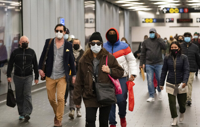 FILE - In this Nov. 17, 2020, file photo, commuters wear face masks while walking through the World Trade Center's transportation hub in New York. Despite the expected arrival of COVID-19 vaccines before the end of 2020, it could be well into 2021 before things get back to something close to normal. (AP Photo/Mark Lennihan, File)