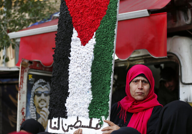 A Palestinian woman holds a symbolic of the Palestine flag with Arabic words that read: