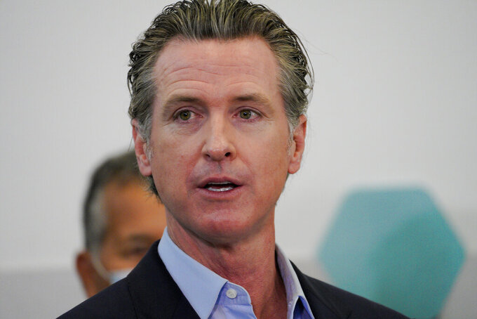 Governor Gavin Newsom speaks with news reporters at Park de la Cruz Recreation Center on Friday, April 2, 2021 in San Diego about the San Diego's newest pop-up vaccination site in the City Heights neighborhood. (Nelvin C. Cepeda/The San Diego Union-Tribune via AP)