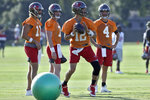 FILE - Tampa Bay Buccaneers quarterback Tom Brady (12) dodges a rolling ball as quarterbacks Blaine Gabbert (11), Reid Sinnett (7), and Ryan Griffin (4) look on during an NFL football organized team activity Thursday, Aug. 13, 2020, in Tampa, Fla. Brady hopes to lead the Buccaneers towards the top. (AP Photo/Chris O'Meara, File)
