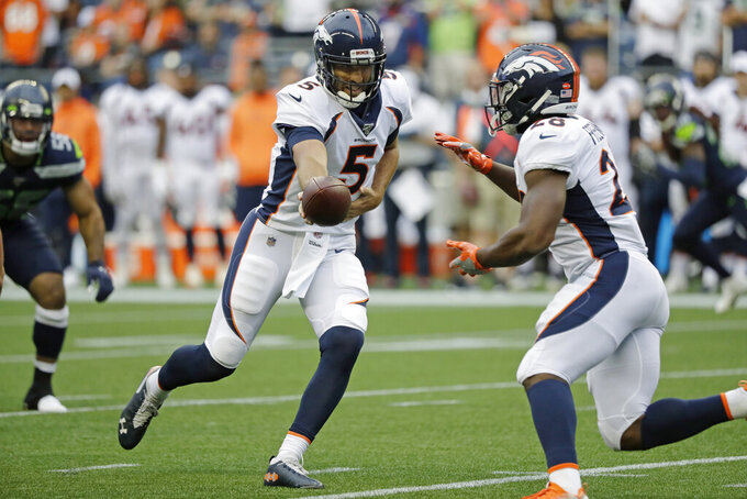 "FILE - In this Aug. 8, 2019, file photo, Denver Broncos quarterback Joe Flacco hands off to running back Royce Freeman, right, during the first half of the team's NFL football preseason game against the Seattle Seahawks in Seattle. ""Joe is the perfect fit for us,"" said Broncos general manager John Elway, who sent the Ravens a fourth-round pick for Flacco, who's making $18.5 million this season. ""He's played in a lot of big games, he has a lot of good football left in him."" (AP Photo/Elaine Thompson, File)"