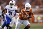 FILE - In this Saturday, Aug. 31, 2019 file photo, Texas's Jordan Whittington (21) runs against Louisiana Tech during the first half of an NCAA college football game in Austin, Texas. Oklahoma State, TCU and Baylor have already had their first games delayed by a week or postponed indefinitely because of virus outbreaks.  And until Texas and UTEP players pass their final Friday, Sept. 11, 2020 COVID-19 tests, their game will remain a question mark.  (AP Photo/Chuck Burton, File)