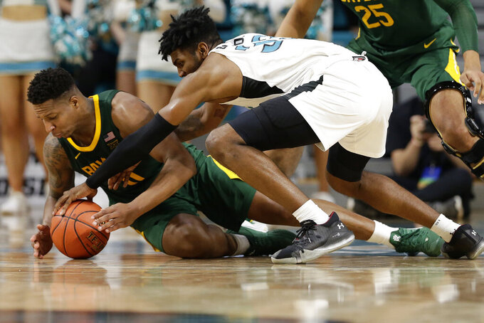 Baylor guard Mark Vital (11) and Coastal Carolina forward Tommy Burton (33) chase the ball during the second half of an NCAA college basketball game at the Myrtle Beach Invitational in Conway, S.C., Friday, Nov. 22, 2019. (AP Photo/Gerry Broome)