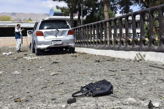 A man takes pictures at the site of a car bomb blast on an intelligence compound in Aybak, the capital of the Samangan province in northern Afghanistan, Monday, July 13, 2020. Taliban insurgents launched a complex attack on the compound that began with a suicide bombing, officials said. (AP Photo)