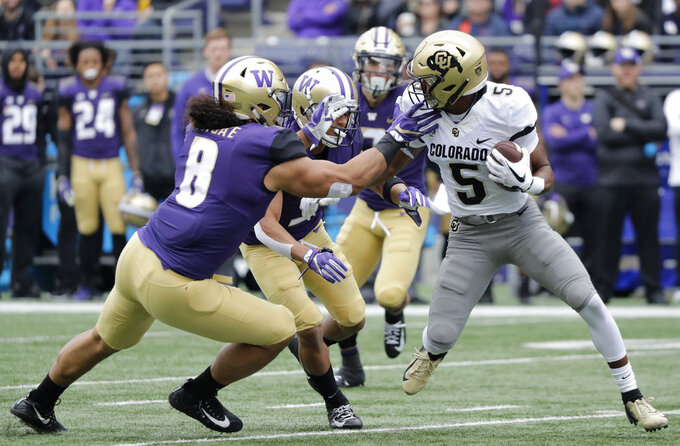 Colorado wide receiver Dimitri Stanley, right, tries to get past Washington linebacker Benning Potoa'e, left, during the first half of an NCAA college football game, Saturday, Oct. 20, 2018, in Seattle. (AP Photo/Ted S. Warren)