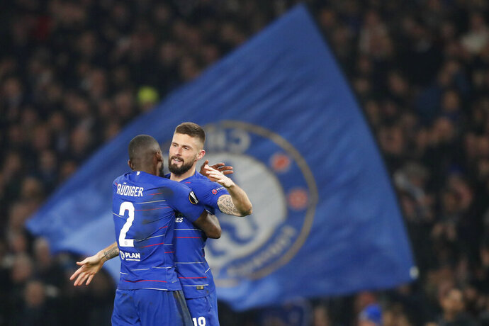 Fans display a large Chelsea flag as Chelsea's Antonio Rudiger, left, hugs Chelsea's Oliver Giroud who scored his side's first goal during the round of 32, second leg, Europa League soccer match between Chelsea and Malmo FF at Stamford Bridge stadium in London, Thursday Feb. 21, 2019. (AP Photo/Frank Augstein)