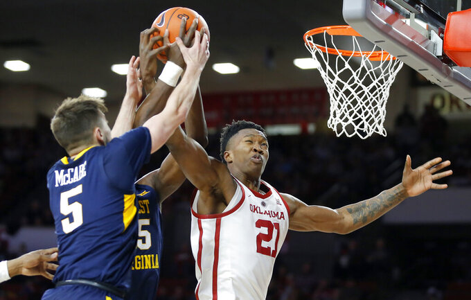 Oklahoma's Kristian Doolittle (21) reaches for the ball against West Virginia's Jordan McCabe (5) and Lamont West (15) during an NCAA college basketball game in Norman, Okla., Saturday, March 2, 2019. (Bryan Terry/The Oklahoman via AP)