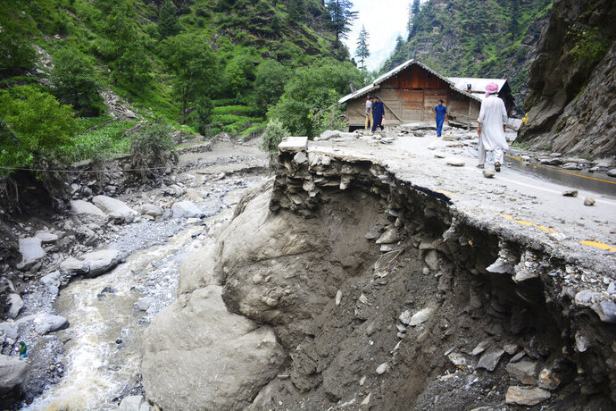 Villagers walk along a road washed away by heavy flooding in Neelum Valley of Pakistani controlled Kashmir, Monday, July 15, 2019. Pakistan says many people are missing and feared dead after heavy rains triggered flash floods in Pakistani-controlled Kashmir. Ahmed Raza Qadri, the Pakistani minister for disaster management in the disputed territory, says the flooding late on Sunday also caused much destruction and damage in the village of Lesswa in Neelum Valley. (AP Photo/M.D. Mughal)