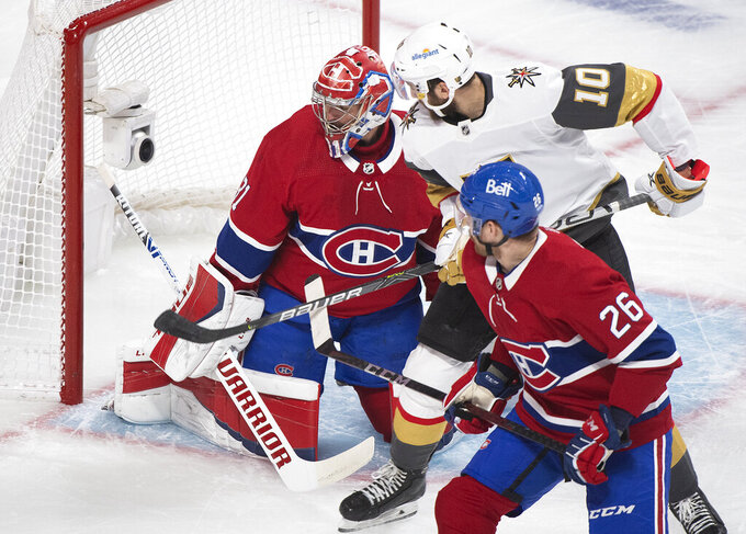 Vegas Golden Knights' Nicolas Roy (10) moves in aagainst Montreal Canadiens goaltender Carey Price as Canadiens' Jeff Petry defends during first-period Game 4 NHL Stanley Cup playoff hockey semifinal action in Montreal, Sunday, June 20, 2021. (Graham Hughes/The Canadian Press via AP)