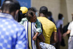 A young child sleeps on a migrant's shoulder after being released from United States Border Patrol custody at a humanitarian center, Wednesday, Sept. 22, 2021, in Del Rio, Texas. (AP Photo/Julio Cortez)