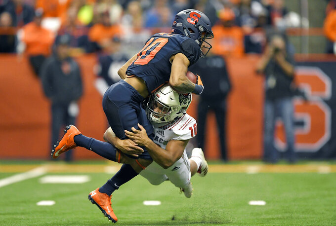NC State defensive back Tanner Ingle, right, tackles Syracuse wide receiver Sean Riley on a kick return during the first half of an NCAA college football game in Syracuse, N.Y., Saturday, Oct. 27, 2018. (AP Photo/Adrian Kraus)