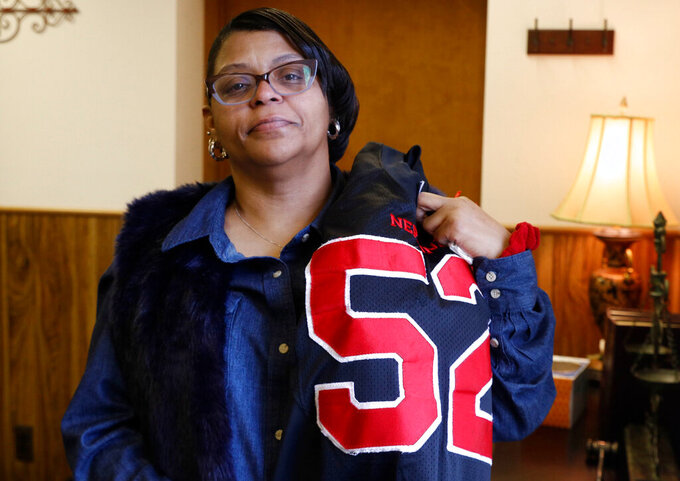 In this Feb. 13, 2019 photo, JoAnne Atkins-Ingram drapes her son's old Neptune High School football jersey over her shoulder in her attorney's office in Avon-by-the-Sea, N.J. Her 19-year-old son, Braeden Bradforth, died in August 2018 about an hour and a half after football practice at Garden City Community College in Garden City, Kan. New Jersey's U.S. House delegation is seeking an independent investigation into Bradforth's death. (Doug Hood/The Asbury Park Press via AP)