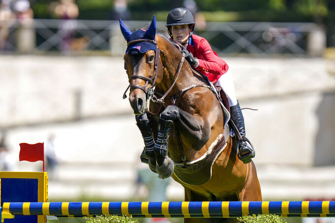 """FILE - In this May 28, 2021, file photo, Jessica Springsteen of the United States, on Don Juan Van de Donkhoeve, clears an obstacle during the Nations Cup horse jumping competition, in Rome. Springsteen, the 29-year-old daughter of Bruce Springsteen, is the """"youngster"""" is making her Olympic debut IN the U.S. equestrian show jumping team for the Tokyo Olympics, where they'll be a new wrinkle – three-person teams instead of four. It's part of an IOC directive to cut down on competitor numbers in some sports. It means that in the team show jumping event, they'll no longer be a fourth, or worst, score to throw out, making it easier for the public and television audiences to understand the scoring system as the event proceeds. (AP Photo/Andrew Medichini,File)"""